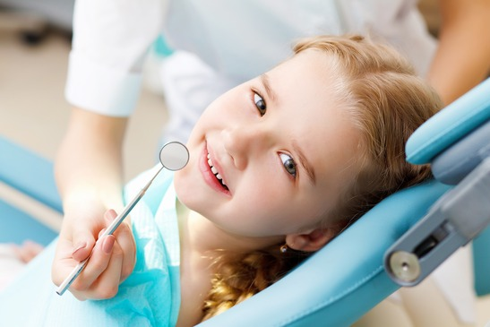 a child smiles at her first dental appointment
