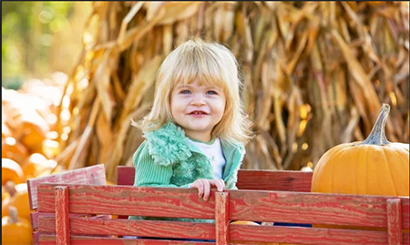 blonde girl in wagon with pumpkin